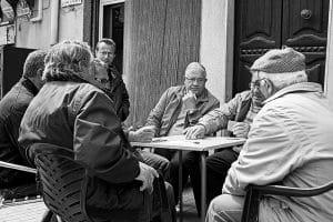 Uomini che giocano a carte, seduti al tavolino di un bar